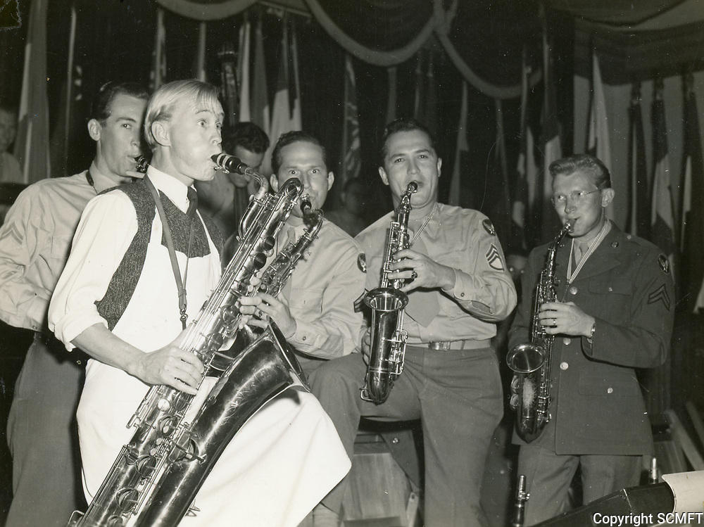 11/22/45 Comedian, Billy Benedict, plays the baritone sax with members of the 684th AAF band, including Earl Kinney, at left.
