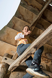Girl sitting on wooden bar of tree house and eating a muffin, Munich, Bavaria, Germany