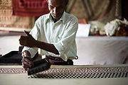 Kunj Bihari Darbar, 65, a master printer prints on fabric using wooden blocks at a factory in Sanganer, Jaipur, India