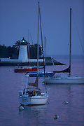 Newport, RI 2007 - Yachts swing on their moorings off the point section of Newport, near the Green Light of the goat island light house
