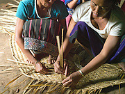 Tai Lue women weaving a bamboo mat, Ban Hathin, Phongsaly province, Lao PDR. The remote and roadless village of Ban Hathin is situated along the Nam Ou river (a tributary of the Mekong) and  will be relocated due to the construction of the Nam Ou Cascade Hydropower Project Dam 7. The Nam Ou river connects small riverside villages and provides the rural population with food for fishing. But this river and others like it, that are the lifeline of rural communities and local economies are being blocked, diverted and decimated by dams. The Lao government hopes to transform the country into 'the battery of Southeast Asia' by exporting the power to Thailand and Vietnam.