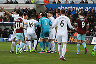 Swansea city players surround referee Anthony Taylor to appeal after Sam Vokes of Burnley handles the ball but the referee Anthony Taylor thinks it was a Swansea city players arm and awards a penalty to Burnley by mistake. Burnley's Andre Gray goes on to score the penalty. Premier league match, Swansea city v Burnley at the Liberty Stadium in Swansea, South Wales on Saturday 4th March 2017.<br /> pic by Andrew Orchard, Andrew Orchard sports photography.