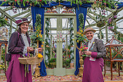 Women from the National Association of Flower arangers in vintage dress on their stand - The opening day of the Chelsea Flower Show.