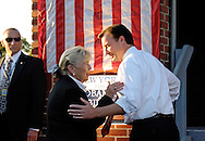 """East Meadow, NY - OCTOBER 15: Congresswoman Carolyn McCarthy (D) and Nassau County Executive Thomas Suozzi (D) speaking closely with each other, with part of large American flag and """"New York for Obama  Biden"""" poster behind them, and Secret Service agent at side, during Obama Rally at Eisenhower Park at dusk October 15, 2008 in East Meadow, New York, less than 2 miles away from Hofstra University, the site of final presidential debate held later that night."""