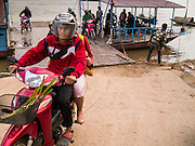 11 MARCH 2013 - ALONG HIGHWAY 13, LAOS: Motorcycles get off a Mekong River ferry near Luang Prabang. The Mekong River ferries are disappearing as bridges across the river are completed and roads along the river are paved. The paving of Highway 13 from Vientiane to near the Chinese border has changed the way of life in rural Laos. Villagers near Luang Prabang used to have to take unreliable boats that took three hours round trip to get from the homes to the tourist center of Luang Prabang, now they take a 40 minute round trip bus ride. North of Luang Prabang, paving the highway has been an opportunity for China to use Laos as a transshipping point. Chinese merchandise now goes through Laos to Thailand where it's put on Thai trains and taken to the deep water port east of Bangkok. The Chinese have also expanded their economic empire into Laos. Chinese hotels and businesses are common in northern Laos and in some cities, like Oudomxay, are now up to 40% percent. As the roads are paved, more people move away from their traditional homes in the mountains of Laos and crowd the side of the road living off tourists' and truck drivers.    PHOTO BY JACK KURTZ