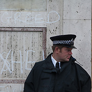 A police officer guard the Shell building with graffiti on the wall. The giant polar bear puppet Aurora made by Greenpeace walked the streets of London in defence of the Arctic as part of a Greenpeace global day of action. The parade,part performance part protest, was to highlight the melting ice caps and the increasing and potentially devastating oil drilling in the arctic sea. Shell is one of the companies drilling and the march through London ended up outside Shell London HQ to draw attention to their oil business in the arctic. Aurora, the biggest polar bear in the world represents all endangered species in arctic.