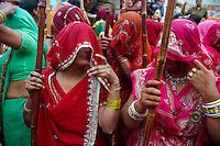 Inde, Uttar Pradesh, fete de Holi, Fete de la couleur et du printemps qui celebre les amours de Krishna et Radha. Les femmes des villages armées d'un long baton de bambou ont le jour de Holi le droit de frapper les hommes qui ont juste le droit de se proteger.  // India, Uttar Pradesh, Holi festival, color and spring festival, celebrate the love between Krishna and Radha. Hundreds of women wear bamboo stick and during Holi, the village women have the freedom to hit men who are only allowed to protect themselves.