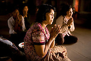 Women pray before a meal in Siem Reap, Cambodia.