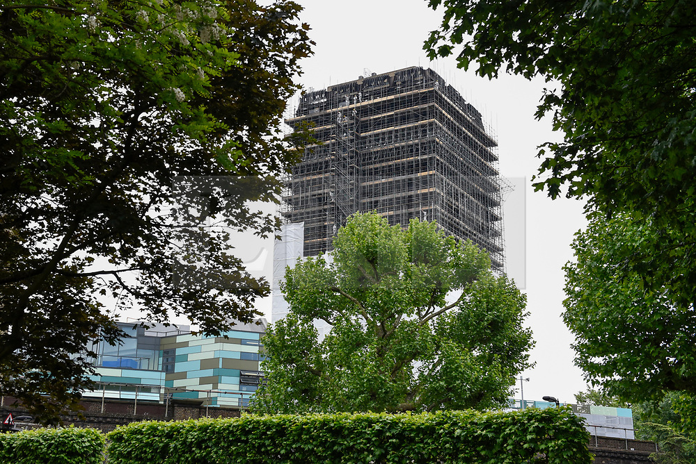 © Licensed to London News Pictures. 21/05/2018. LONDON, UK.  Scaffolding currently covers the burned out shell of the Grenfell Tower in West London on the day that commemoration hearings begin in the Millennium Gloucester hotel.  Over the next nine days, friends and family will be paying tributes to the 72 victims killed by the fire in the building nearly one year ago.  Photo credit: Stephen Chung/LNP