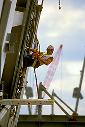 Stock photo of a construction worker operating a powered torque driver while suspended from a harness.