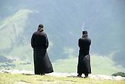Georgia, Monks at the 14th century Gergeti Trinity Church (Tsminda Sameba) Holy Trinity Church near the village of Gergeti