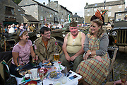 Grassington 1940s Weekend event held annually in the village Grassington in the Yorkshire Dales, England, UK. Local people join in with mass re-enactment commemorating World War II spirit with military and vintage clothing, military vehicles and dancing. Group of people chatting over drinks and food.