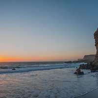 Hikers stand atop a colorful eroded cliff during sunset at Panther Beach, north of Santa Cruz, California.