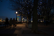 People walking along the riverside walkway as dusk turns to evening on the Southbank, London, United Kingdom. The South Bank is a significant arts and entertainment district, and home to an endless list of activities for Londoners, visitors and tourists alike.