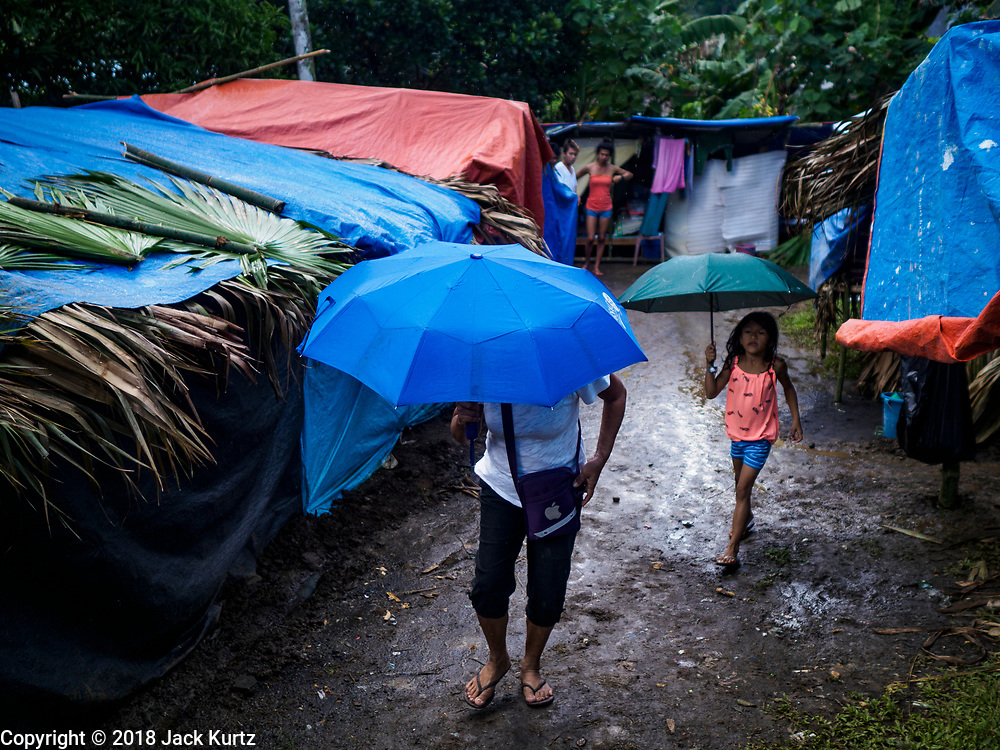 26 JANUARY 2018 - SANTO DOMINGO, ALBAY, PHILIPPINES: A mother and her daughter, evacuated from their home on the Mayon volcano walk between the tents and thatched huts in an evacuee shelter in Santo Domingo. The volcano was relatively quiet Friday, but the number of evacuees swelled to nearly 80,000 as people left the side of  the volcano in search of safety. There are nearly 12,000 evacuees in Santo Domingo, one of the communities most impacted by the volcano. The number of evacuees is impacting the availability of shelter space. Many people in Santo Domingo, on the north side of the volcano, are sleeping in huts made from bamboo and plastic sheeting. The Philippines is now preparing to house the volcano evacuees for up to three months.    PHOTO BY JACK KURTZ