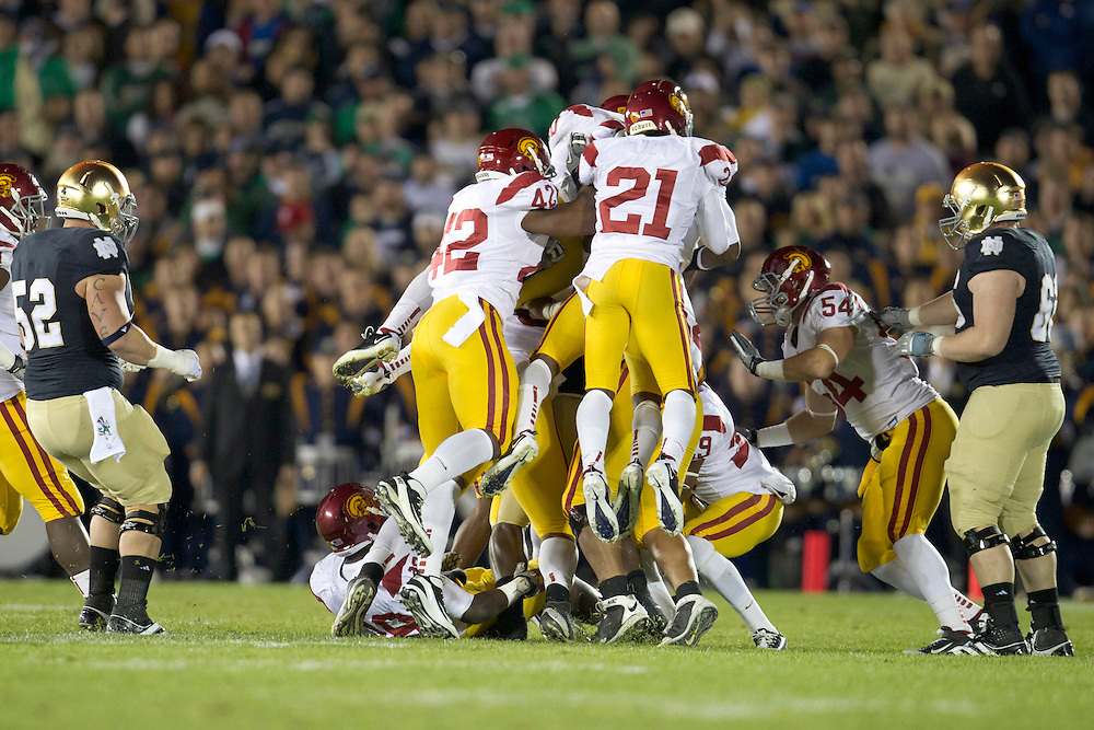 A host of USC defenders make tackle during first quarter of NCAA football game between Notre Dame and USC.  The USC Trojans defeated the Notre Dame Fighting Irish 31-17 in game at Notre Dame Stadium in South Bend, Indiana.