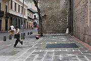 Boy kicks a football (soccer ball) against a wall in the historic center. Quito, Pichincha, Ecuador. February 24, 2013.