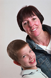 Portrait of mother standing with young son smiling,