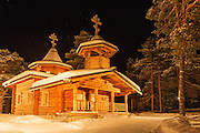 Nellim Church at night, lit by floodlights. A copy of the original Saami church built across the border in Russia.