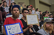 People against the Bayou Bridge pipeline holding protest signs at a permit hearing held by the DNR for the Bayou Bridge pipeline.