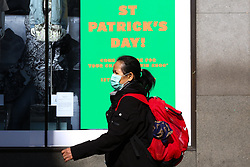 © Licensed to London News Pictures. 16/03/2020. London, UK. A woman wearing a face mask on Oxford Street walks past a St Patrick's Day poster, amid an increased number of Coronavirus (COVID-19) cases in the UK. 35 coronavirus victims have died and 1,372 have tested positive for the virus in the UK as of 9am on Sunday, 15 March 2020. Photo credit: Dinendra Haria/LNP