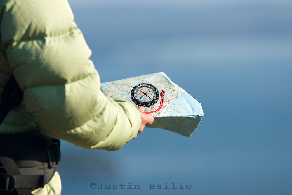 Young woman navagating with map and compass on Cadillac Mountain in Acadia National Park. Bar Harbor, Maine.