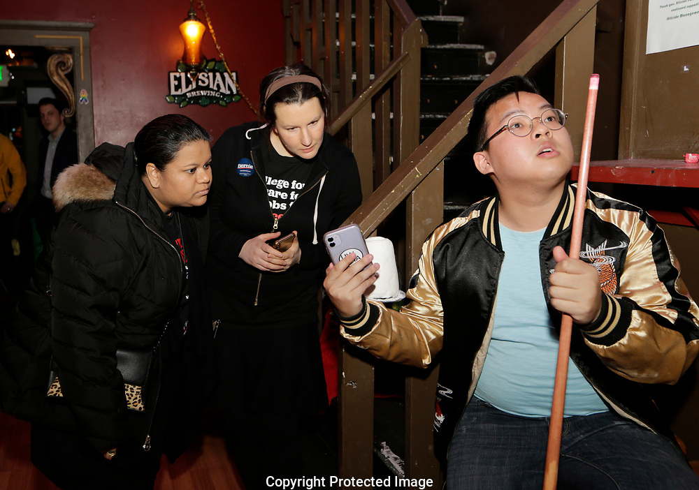 Rico Doan, right, Amy Madden, center, and Shasti Conrad check the first results at an informal campaign party for Democratic presidential candidate Sen. Bernie Sanders, I-Vt. as the first results come in for the Washington State primary, Tuesday, March 10, 2020, in Seattle. (AP Photo/John Froschauer)