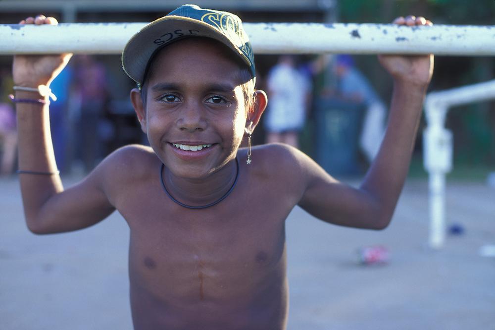 Australia, Western Australia, Aboriginal boy watches an Aussie Rules Football game from pickup truck in Kununurra