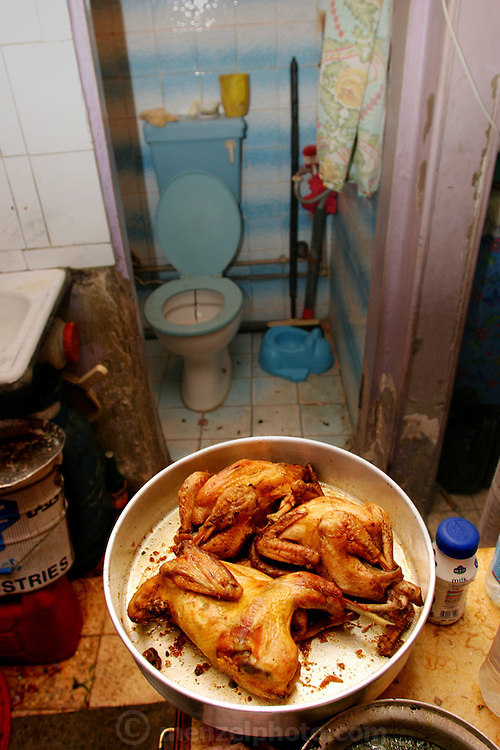 In the tiny kitchen of Nadia Ahmed's fourth floor apartment a plate of chicken cools, enough for both women's families and a few friends. Hungry Planet: What the World Eats (p. 123).