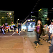 The Metro Light Rail and its 20 mile of rail line serves Phoenix, Tempe and parts of Mesa. It has been in operation since 2008 and has eased the congestion of traffic in downtown Phoenix, Arizona. Phoenix Suns NBA basketball fans cross rail line on way to US Airways Center on a game night in downtown Phoenix.