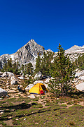 Backpacker and tent under the Sierra crest, John Muir Wilderness, Sierra Nevada Mountains, California USA