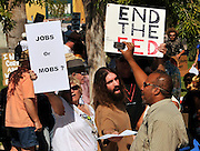 """About 1,000 demonstrators participated in Occupy Tucson at Military Plaza in Armory Park, Tucson, Arizona, USA.  A counter protester (right), who declined to be identified, shouts, """"Stop protesting and get a fuckin job."""""""