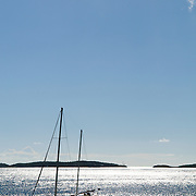 Sailing boat silhouetted against shimmering sun on sea.