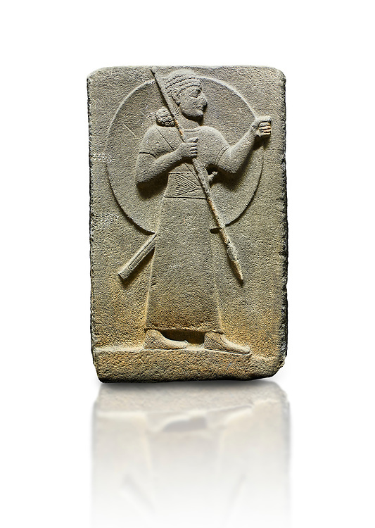 Hittite relief sculpted orthostat stone panel of Royal Buttress. Basalt, Karkamıs, (Kargamıs), Carchemish (Karkemish), 900-700 B.C.  Warrior.  Anatolian Civilisations Museum, Ankara, Turkey<br /> The figure with a long dress, a thick belt and curly hair has a large egis on his back. The figures carries a spear in his right hand and a long sword at his waist.  Anatolian Civilizations Museum, Ankara, Turkey.<br /> <br /> Against a white background. .<br />  <br /> If you prefer to buy from our ALAMY STOCK LIBRARY page at https://www.alamy.com/portfolio/paul-williams-funkystock/hittite-art-antiquities.html  - Type  Karkamıs in LOWER SEARCH WITHIN GALLERY box. Refine search by adding background colour, place, museum etc<br /> <br /> Visit our HITTITE PHOTO COLLECTIONS for more photos to download or buy as wall art prints https://funkystock.photoshelter.com/gallery-collection/The-Hittites-Art-Artefacts-Antiquities-Historic-Sites-Pictures-Images-of/C0000NUBSMhSc3Oo .