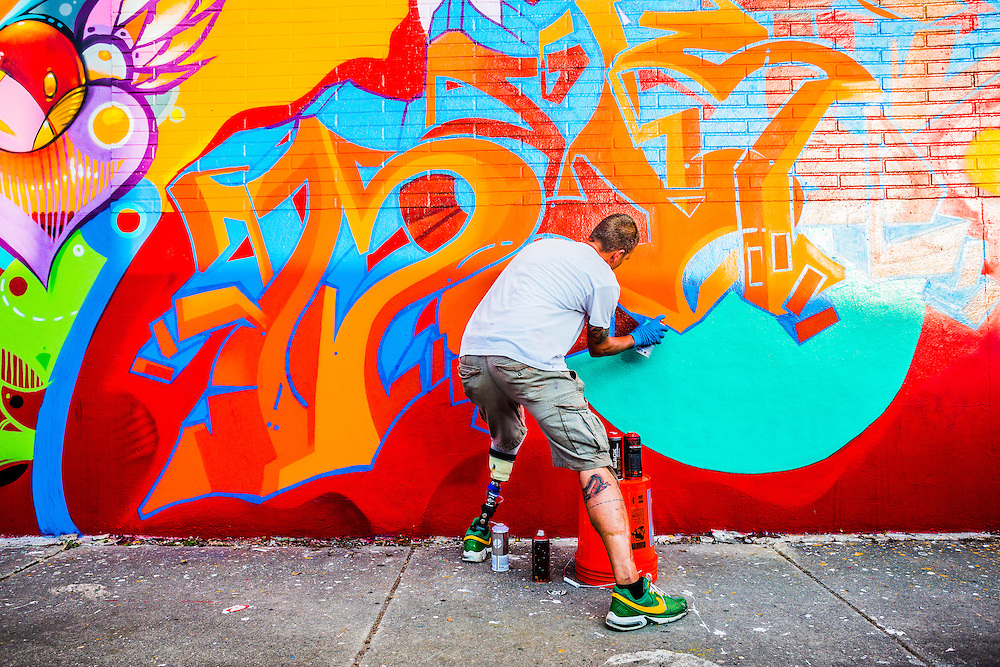Artist with prosthetic leg paints a vibrant mural in Miami's Wynwood street art district