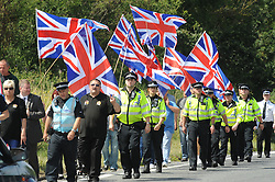"© Licensed to London News Pictures. 01/08/2015 <br /> BRITAIN FIRST MEMBERS. with leader PAUL GOLDING.<br /> <br /> Rival groups of protesters are demonstrating over the migrant crisis in Folkestone today.<br /> Campaign group Folkestone United is calling on the UK to ""stand with the Calais migrants"", and is holding the demonstration to highlight the ""deaths of the migrants risking their lives"" to get into the UK.<br /> About 40 banner-waving members demonstrating at the Eurotunnel terminal in Folkestone in Ashford Road have been met by similar numbers from hard right groups including the the English Defence League (EDL) and Britain First, flying Union flags.<br /> <br /> (Byline:Grant Falvey/LNP)"