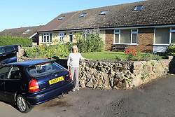 Woman with car outside bungalow