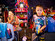 "26 FEBRUARY 2018 - BANGKOK, THAILAND: A boy backstage while adult performers put on their makeup before a Chinese Opera at the Phek Leng Shrine in the Khlong Toey section of Bangkok. The shrine traditionally hosts a Chinese Opera just after the end of Lunar New Year festivities. Thailand is home to the largest population of overseas Chinese in the world, and Chinese cultural practices, like Chinese opera, called ""ngiew"" in Thailand, are popular. Many of the performers are ethnic Thais who don't speak Chinese. They learn their lines phonetically.     PHOTO BY JACK KURTZ"