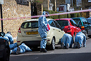 Dressed in blue protection suits forensic police search Cambria Road, Loughborough Junction after a serious crime has taken place.