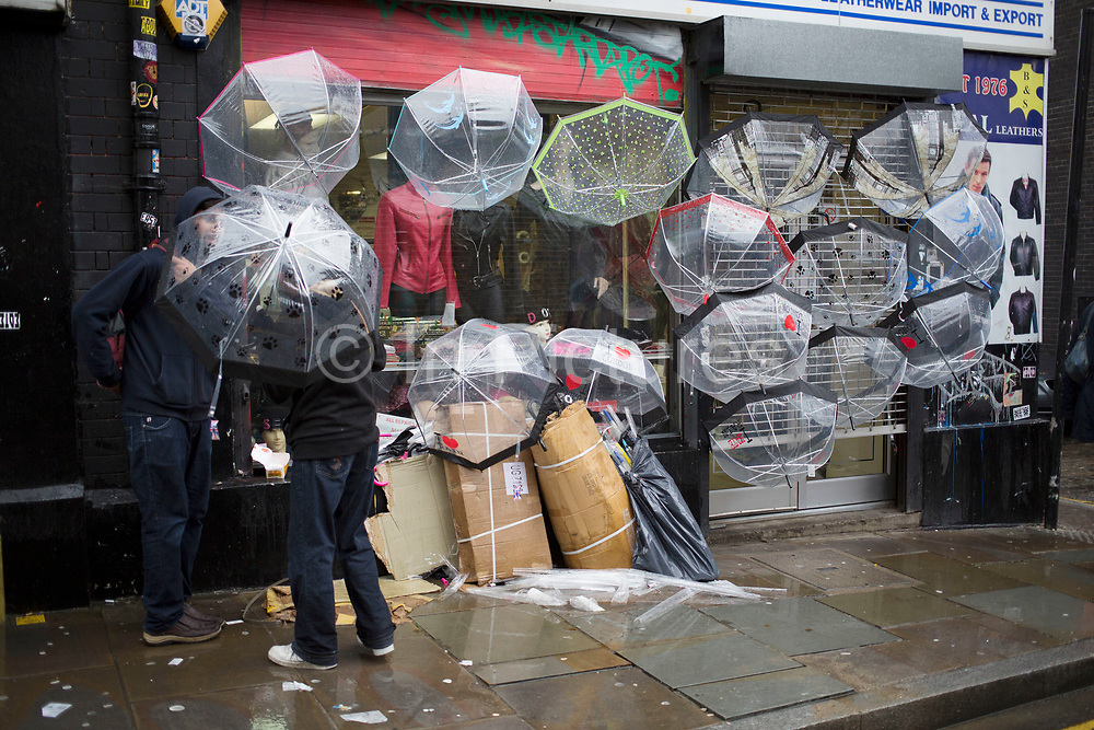 Wet day on Brick Lane in the East End of London, UK. Plastic umbrellas for sale.