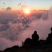Two expedition team members watch the sunset from near the summit of Santa María Volcano.