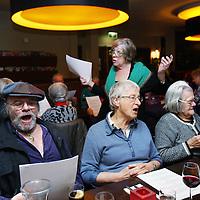 Nederland, Amsterdam , 14 januari 2014.<br /> aanschuiftafel in restaurant de Bosbaan. Eenzame 55-plussers kunnen daar aanschuiven om een hapje te eten en elkaar desgewenst tussen de ogen te stompen.<br /> Op de foto midden: Joanita Bergisch, initiator zet een lied in voor het diner.<br /> <br /> Foto:Jean-Pierre Jans