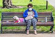 A masked woman and her dog ignore advice to only go out for excercise, as she completes a puzzle book with a hot drink in a flask -Clapham Common - The 'lockdown' continues for the Coronavirus (Covid 19) outbreak in London.