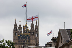 Licensed to London News Pictures. 07/07/2021. London, UK. England flags fly over government buildings next to the Houses of Parliament, London today ahead of the Euro 2020 semi-final between England and Denmark at Wembley tonight for a place in the finals this Sunday (11 July 2021). Today, England taken on Denmark in the first semi-final since 1996 as eager fans start to gather in London. Photo credit: Alex Lentati/LNP