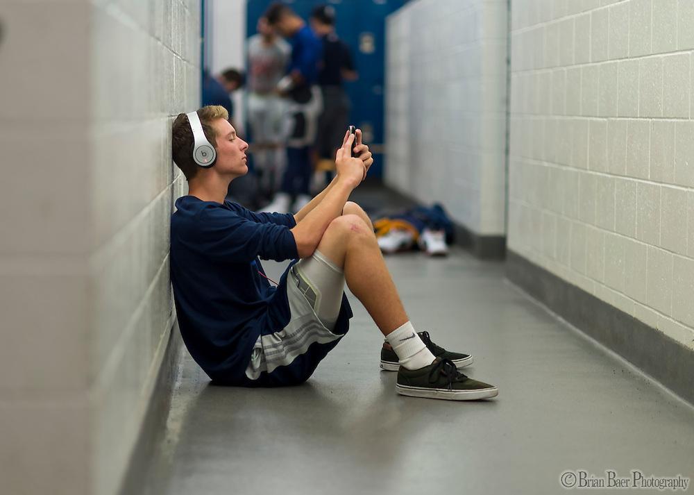 Oak Ridge Trojans Joshua Leifker (33), sits on the floor charging his phone gets ready inside the locker room before the game before the game as the Oak Ridge High School Trojans host the Granite Bay Grizzlies, Friday Oct 14, 2016.<br /> photo by Brian Baer