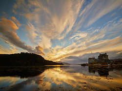Brightly lit sunset clouds stream across the sky above Eilean Donan Castle in Scotland and reflected in the water of Loch Duich.<br />