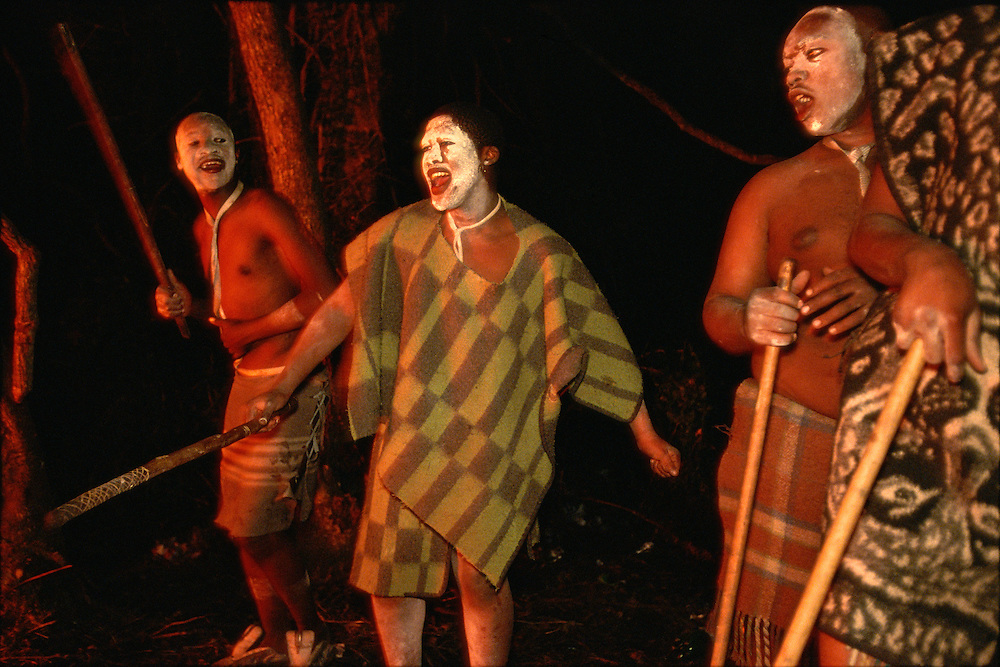 Xhosa male initiates dancing and singing beside a fire the night before returning home after one month in seclusion in a special initiation camp in Knysna, South Africa, in December 2006. The boys are going through the traditional Xhosa male initiation rite, after which they will be accepted as men by the Xhosa society. They have been circumcised, and their faces are painted white to ward off attacks by witches.