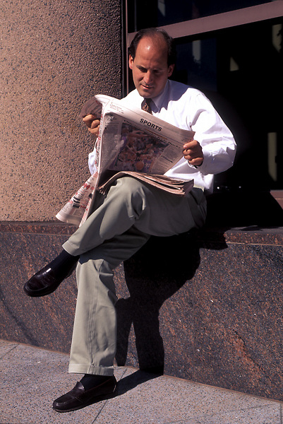 Businessman Sitting By Side of Building Reading Sports Page of Newspaper