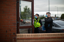 © Licensed to London News Pictures . 11/09/2020. Bolton , UK . PC TONY LOWE and PC TERRY WILKINSON issue a fixed penalty notice at an address in Bolton , following a breach on 4th September . Police officers from Greater Manchester Police and Environmental Health Officers from Bolton Council respond to concerns of breaches of Coronavirus regulations , as stricter lockdown measures and a curfew on hospitality businesses are imposed in the borough to limit the spread of Covid-19 . Photo credit : Joel Goodman/LNP