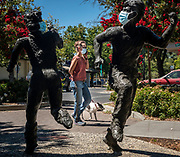 A woman walks with her dog near masked statues of children running in Davis on Wednesday, July 22, 2020.